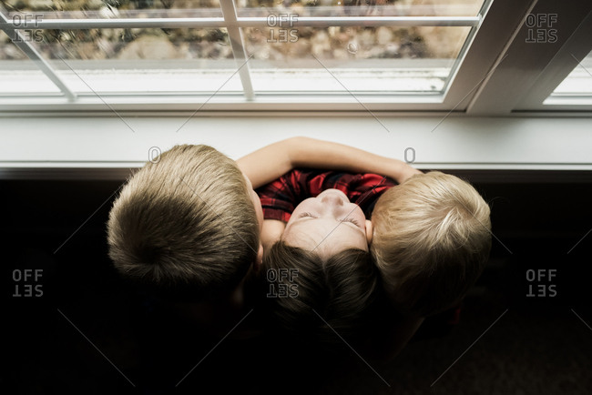 High angle view of siblings embracing while standing by window at home