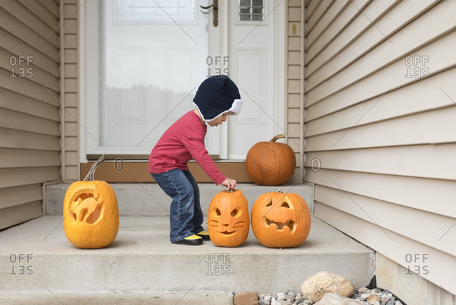 Side view of baby boy holding jack o lantern while standing at entrance