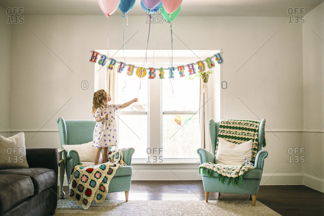 Girl decorating balloons in living room for birthday party