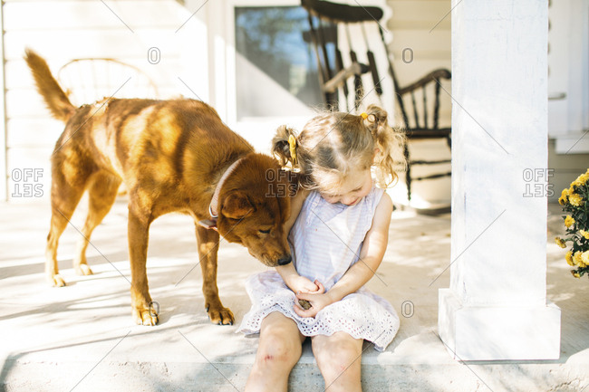 Dog playing with girl on porch