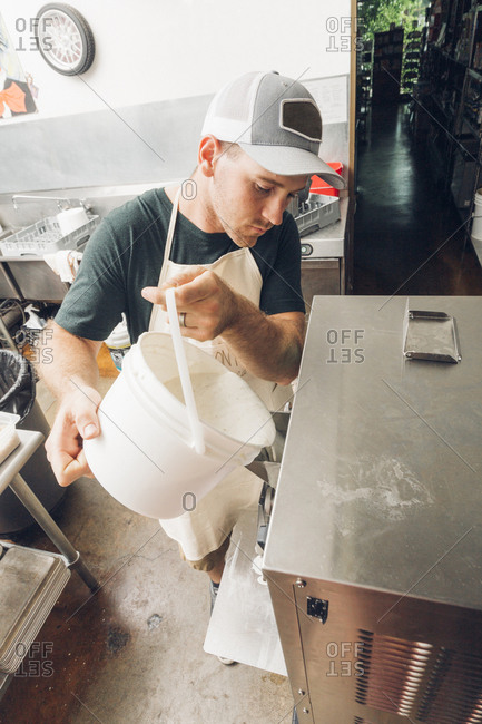 Man pouring ingredients in ice cream maker at commercial kitchen