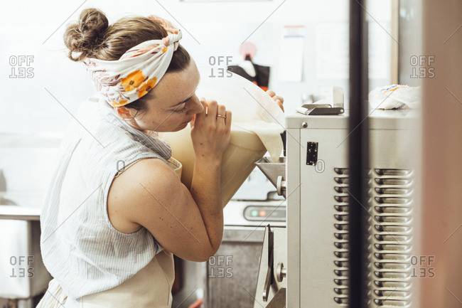 Woman pouring ingredients in ice cream maker at commercial kitchen
