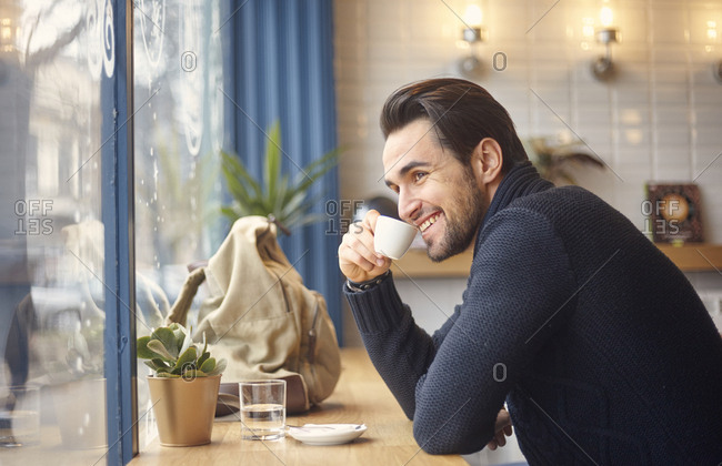 Side view of smiling man looking through window while having coffee by window at cafe