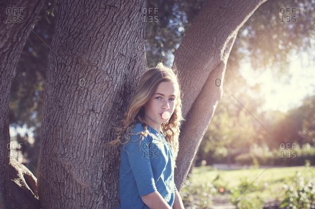 Portrait of confident girl blowing bubble gum against tree trunk at park