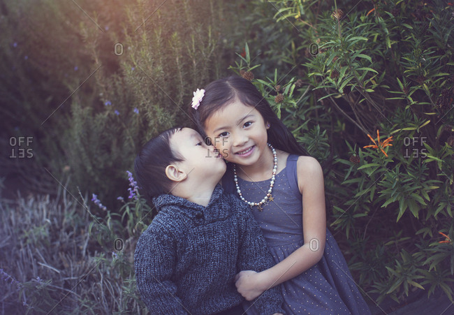 Portrait of cute sister with brother kissing her against plants at park