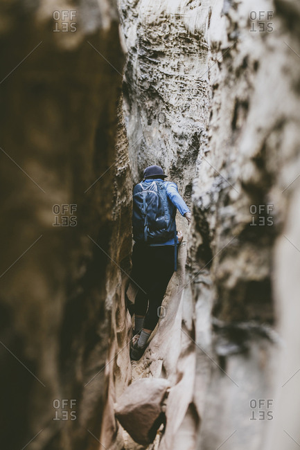 Rear view of hiker with backpack amidst narrow rock formations