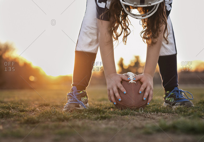 Low section of girl holding American football while standing on grassy field against sky during sunset