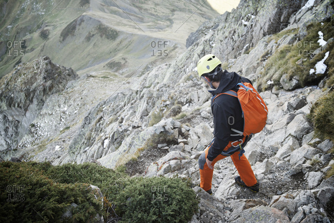 High angle view of hiker with backpack standing on rocks during mountain climbing