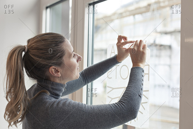 Woman hanging up business sign on storefront window