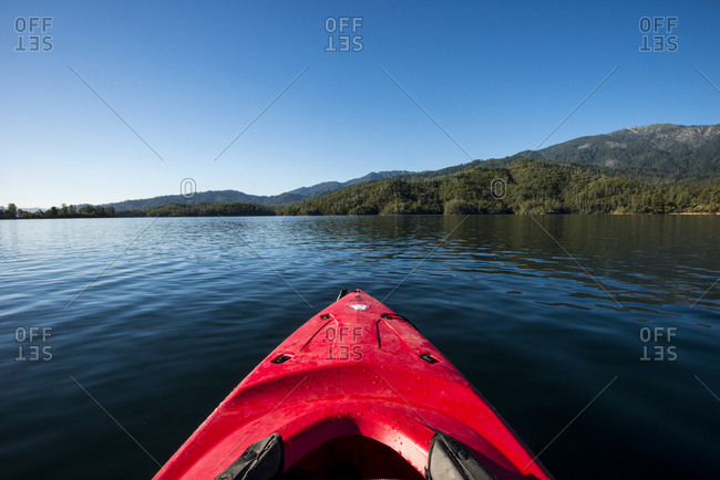 California, USA - September 13, 2016: Looking out over the bow of a red kayak on Whiskeytown Lake near Redding, California