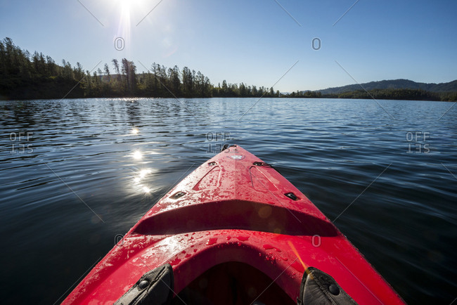 California, USA - September 13, 2016: Looking out over the bow of a red kayak on Whiskeytown Lake in the summer near Redding, California