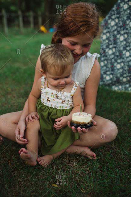 Big sister giving baby sister cake in backyard