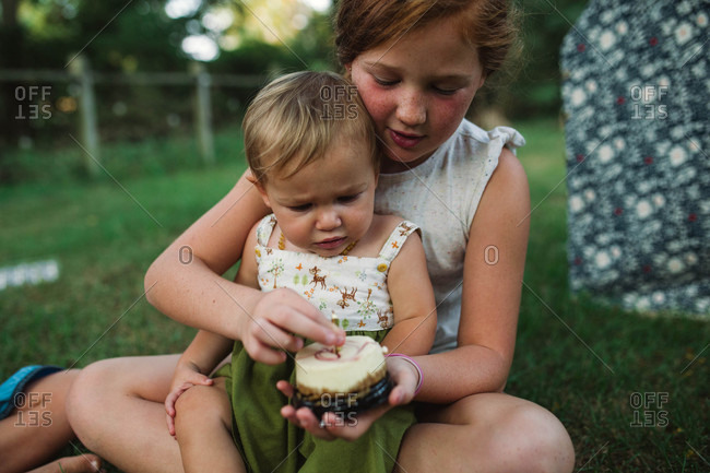 Older sister showing baby how to eat her cake