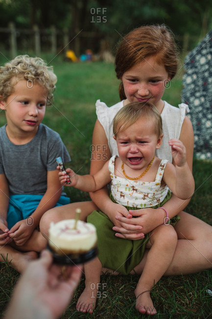 Baby sister frustrated with family at backyard picnic