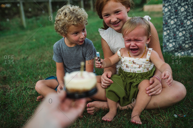 Siblings try to comfort crying birthday baby