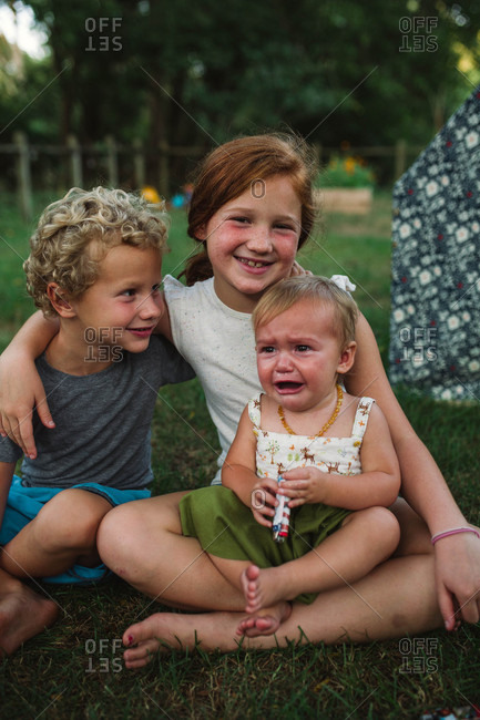 Two kids sitting in the grass with cranky baby