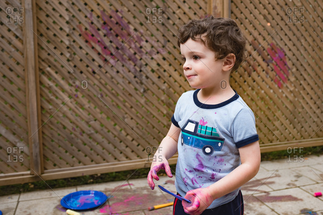 Young boy looking concerned after painting on fence and on himself