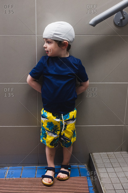 Little boy wearing swim trunks and swim cap standing against wall