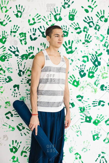 Young man holding rolled yoga mat standing in front of wall decorated with hand prints