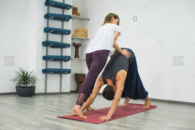 Yoga instructor helping young man in downward facing dog position
