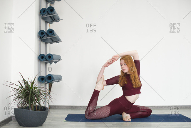 Young woman in variation of half pigeon yoga pose