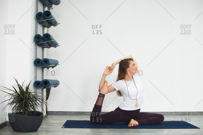 Side view of young woman in variation of half pigeon yoga pose