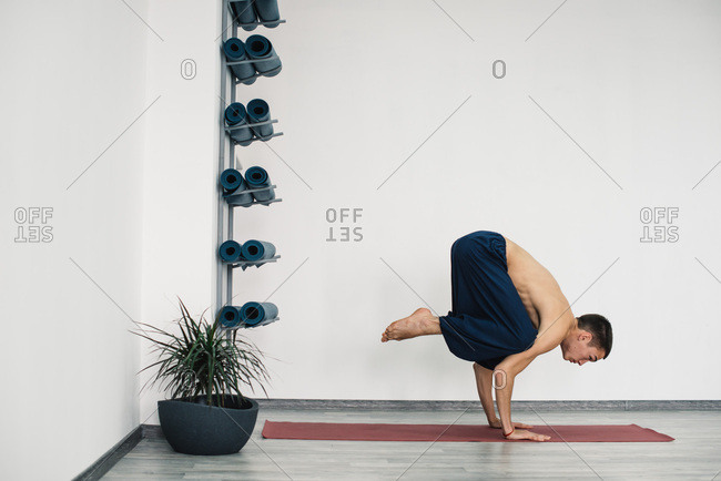 Young man balancing in crow yoga pose