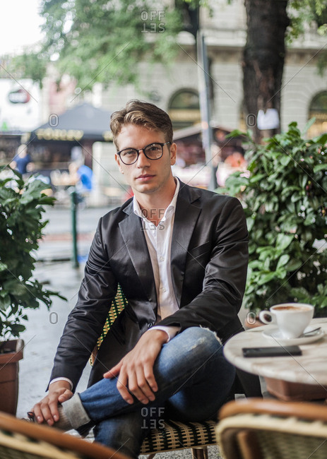 Portrait of young man sitting at outside cafe table
