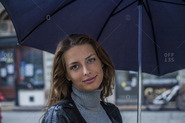 Portrait of young woman holding umbrella in the rain