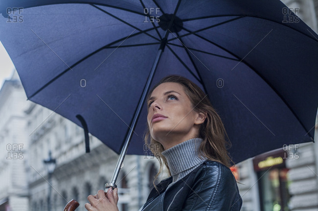 Young woman, contemplating the weather under an umbrella