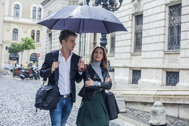 Young businessman and businesswoman, walking in the street, under an umbrella