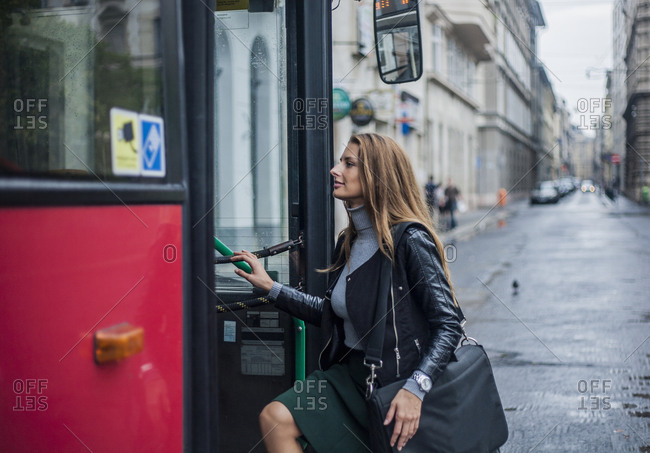Young businesswoman commuter getting on city bus