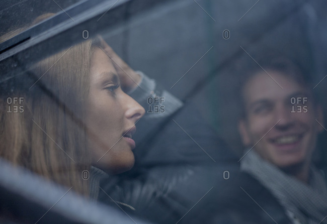Young man and woman chatting on a bus, exterior