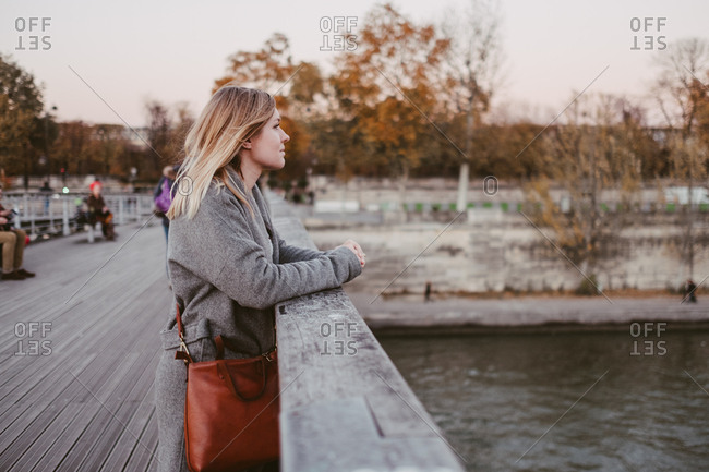 Woman looking out at the Seine river in Paris from a bridge