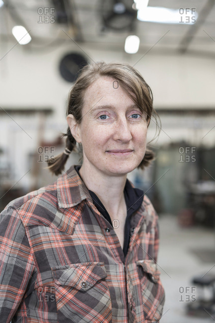 Blond woman wearing checked shirt standing in metal workshop, smiling at camera