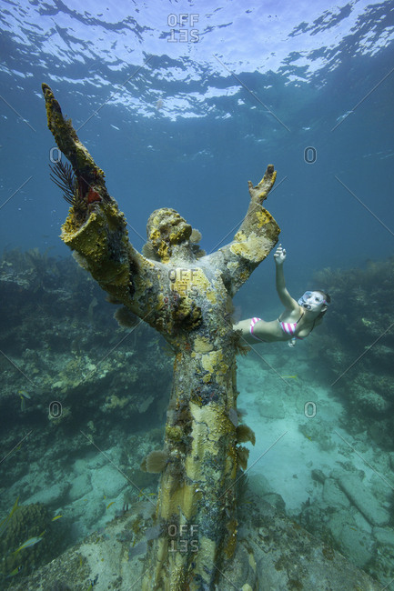 A young woman snorkels near the Christ of the Abyss Statue. The bronze statue was submerged in the waters of Key Largo in 1965