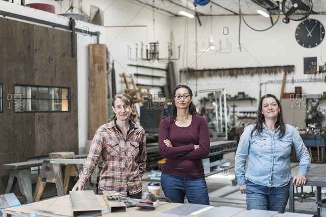 Three women standing in metal workshop, holding looking at camera