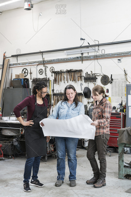Three women standing in metal workshop, holding technical blueprint
