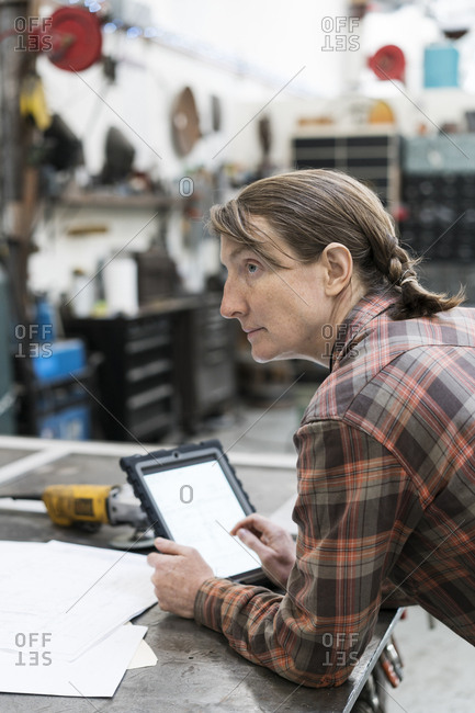 Side view of blond woman wearing checked shirt standing at workbench in metal workshop, holding digital tablet