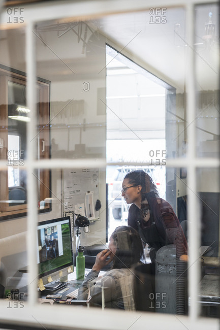 Two women looking at computer screen in office area of metal workshop