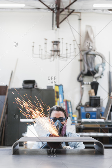 Woman wearing safety glasses and dust mask standing in metal workshop, using power grinder, sparks flying