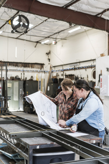 Two women standing at workbench in a metal workshop, looking at technical blueprint