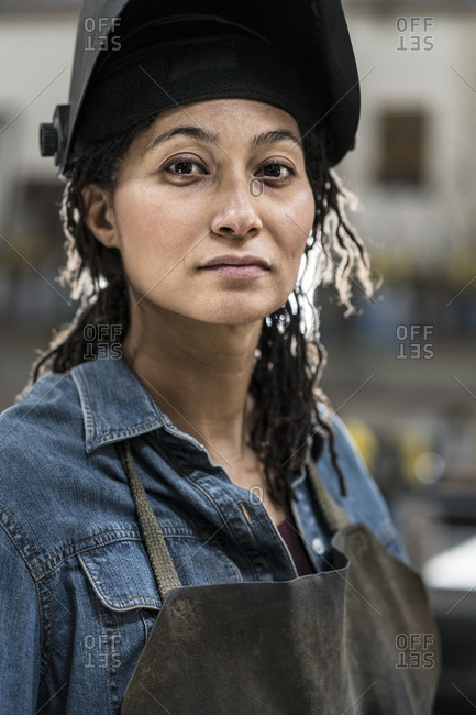 Portrait of woman wearing apron and welding mask standing in metal workshop, smiling at camera