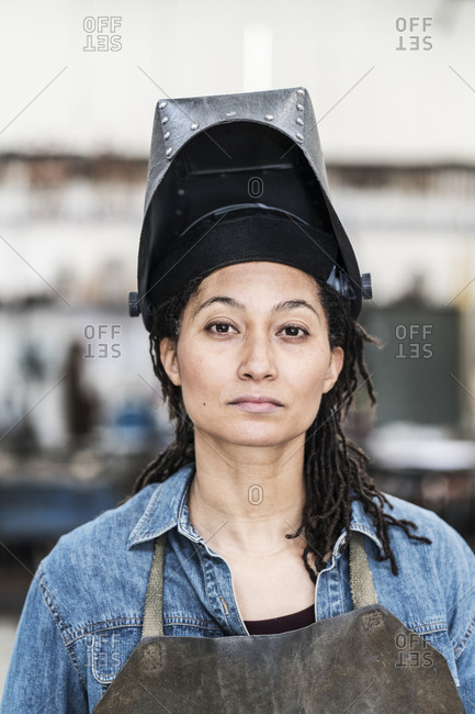 Portrait of woman wearing apron and welding mask standing in metal workshop, looking at camera