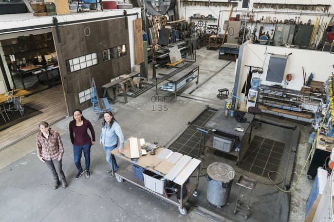 High angle view of three women standing in metal workshop, looking at camera