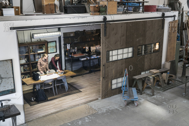 High angle view of two women gathered around table in office area of metal workshop
