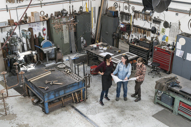 High angle view of three women standing in metal workshop, holding technical blueprint
