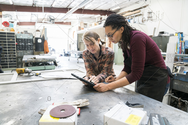 Two women standing at workbench in metal workshop, looking at digital tablet
