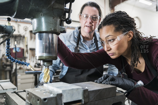 Two women wearing safety glasses standing in a metal workshop, working on metal drilling machine