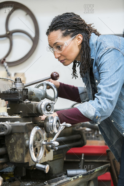 Woman wearing safety glasses standing in a metal workshop, working at metal lathe machine